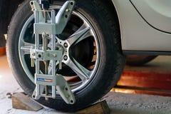 L'automobile sul supporto con i sensori sulle ruote per la curvatura di allineamento di ruote controlla l'officina del distributo Immagine Stock Libera da Diritti