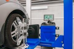 L'automobile sul supporto con le ruote dei sensori per la curvatura di allineamento controlla l'officina del distributore di benz Immagini Stock Libere da Diritti