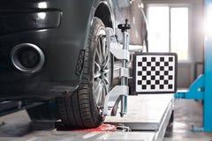 L'automobile sul supporto con le ruote dei sensori per la curvatura di allineamento controlla l'officina del distributore di benz Fotografia Stock