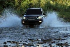 L'automobile SUV sormonta una torrente montano all'alta velocità Fotografie Stock Libere da Diritti