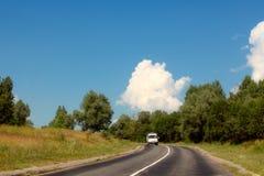 L'automobile va sulla strada principale nel mezzo degli alberi Immagini Stock Libere da Diritti