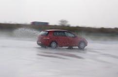 L'automobile veloce ha indotto aquaplanning durante il corso di azionamento avanzato Fotografia Stock Libera da Diritti