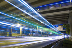 L'autoroute dans la nuit avec des véhicules s'allument dans la ville moderne. image stock