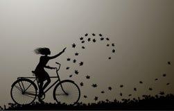 L'autunno viene, guida della ragazza sulla bicicletta e foglie di autunno che turbinano, siluetta, in bianco e nero, illustrazione vettoriale