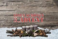 L'avènement de décoration de Joyeux Noël brûlant la bougie grise a brouillé l'Allemand 3ème de message textuel de neige de fond Image stock