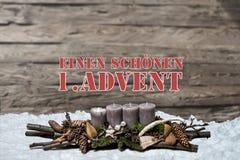 L'avènement de décoration de Joyeux Noël brûlant la bougie grise a brouillé l'Allemand 1er de message textuel de neige de fond Photo stock