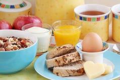 L'avena sana della prima colazione si sfalda, l'uva passa, i dadi, mele secche, egg, pane integrale, formaggio, mele, succo d'ara Fotografia Stock Libera da Diritti