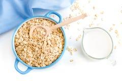 L'avena si sfalda piatto con latte, arancia, uova su una tavola bianca di legno Il punto di vista superiore dell'avena sana si sf Fotografie Stock