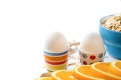 L'avena si sfalda piatto con latte, arancia, uova su una tavola bianca di legno Il punto di vista superiore dell'avena sana si sf Immagini Stock