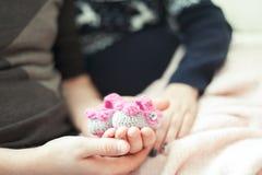 L'avenir heureux parents des mains tenant le bébé nouveau-né tricoté de laine Photo libre de droits