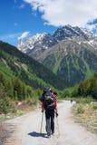 L'aventurier d'homme avec le grand chien marche sur la route dans un gorg de montagne Photographie stock