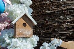 L'aviario con il tetto bianco sui precedenti di un mazzo di rami e di molla sottili fiorisce immagini stock