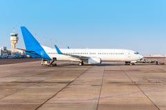 L'avion à l'aéroport avec tour de contrôle sur le chargement Photo libre de droits