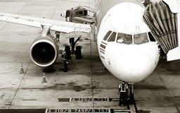 L'avion avec la passerelle de débarquement à l'aéroport international Photos stock