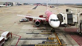 L'avion avec la passerelle de débarquement à l'aéroport international Photographie stock libre de droits