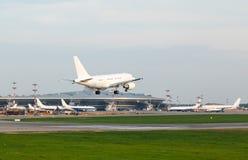 L'avion blanc débarque sur la piste sur le fond de l'aéroport Photographie stock