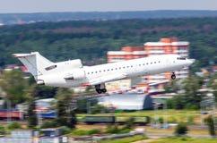 L'avion blanc décollent dans la perspective du secteur industriel de la ville et de la forêt photographie stock