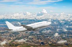L'avion blanc de passager vole montant au-dessus de l'de grands megaopolis, ville Image libre de droits