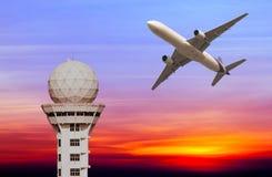 L'avion commercial décollent au-dessus de tour de contrôle d'aéroport au sunse Images stock