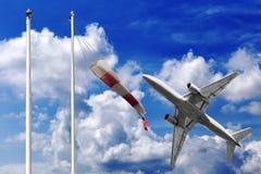L'avion décolle dans un beau ciel d'été avec le manche à air rouge et blanc Images stock