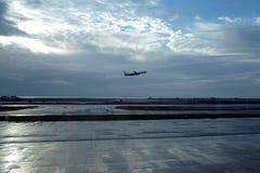 L'avion décolle tôt le matin de la piste de l'aérodrome à l'aube et de la mer dans la distance Image stock