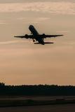 L'avion décollent sur le coucher du soleil de l'aéroport Photos stock