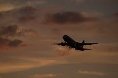 L'avion décollent sur le coucher du soleil de l'aéroport Photographie stock