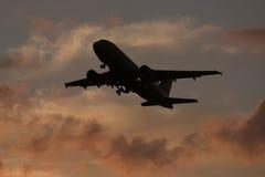 L'avion décollent sur le coucher du soleil de l'aéroport Photo libre de droits