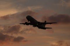 L'avion décollent sur le coucher du soleil de l'aéroport Photos libres de droits