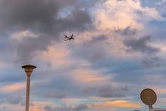 L'avion décore en vol le ciel nuageux de Barcelone Photos stock