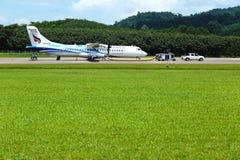 L'avion d'ATR 72-600 sur la piste de taxi d'aéroport avec des herbes mettent en place Photo libre de droits