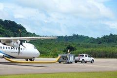 L'avion d'ATR 72-600 sur la piste de taxi d'aéroport avec des herbes mettent en place Photos libres de droits
