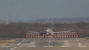 L'avion de passagers argenté débarque lentement sur la piste d'atterrissage à l'aéroport le jour ensoleillé banque de vidéos