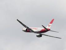 L'avion de passagers rouge et blanc TU-204-100BE, rouge s'envole la ligne aérienne Image libre de droits