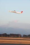 L'avion de turbopropulseur décolle tandis que le volcan fait éruption Images libres de droits