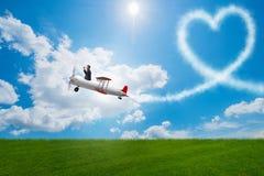 L'avion de vol d'homme et fabrication de la forme de coeur Photographie stock