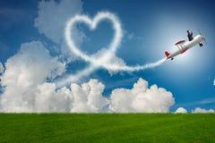 L'avion de vol d'homme et fabrication de la forme de coeur Photos libres de droits