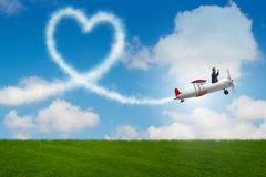L'avion de vol d'homme et fabrication de la forme de coeur Image stock
