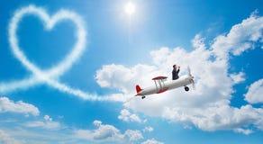 L'avion de vol d'homme et fabrication de la forme de coeur Photographie stock libre de droits
