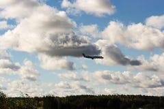 L'avion est dans les nuages au-dessus de la terre Photos stock