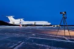 L'avion est garé à l'aéroport la nuit et l'appareil-photo est sur un trépied Photo stock