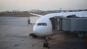 L'avion est près du terminal dans l'aéroport international au crépuscule Image stock