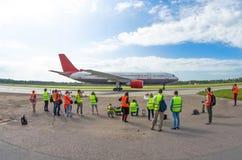 L'avion est prêt pour le départ et le décollage, une foule des personnes voit outre de l'avion Photographie stock libre de droits