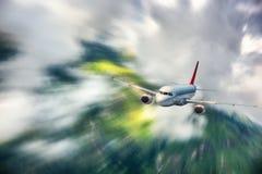 L'avion moderne avec l'effet de tache floue de mouvement vole en nuages au coucher du soleil Avion de passager Image libre de droits