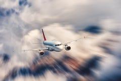 L'avion moderne avec l'effet de tache floue de mouvement vole en nuages plus de Photo stock