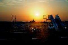 L'avion quitte l'aéroport sur le coucher du soleil - beau paysage Images stock