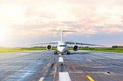 L'avion roule au sol avant décolle le soir au coucher du soleil à l'aéroport Photos libres de droits