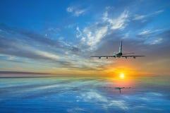 L'avion s'élève, volant au-dessus de la mer vers le soleil au coucher du soleil Images libres de droits