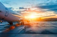 L'avion s'est garé à l'aéroport à l'aube dans le soleil de nuages de ciel Photos libres de droits