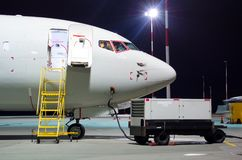 L'avion s'est garé à l'aéroport la nuit, habitacle de nez de vue Photos stock